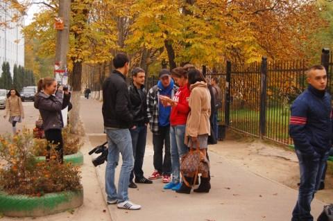 Студенти читають листівку, а дівчина із студпарламенту намагається це сфотографувати.