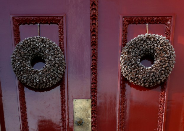 pinecone wreaths on red doors