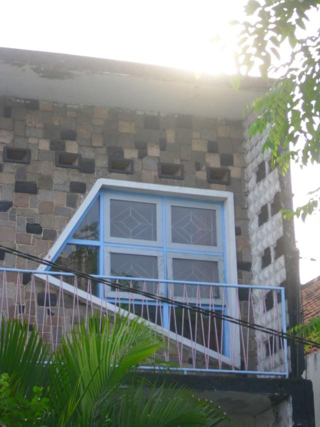 ingkai jendela miring-miring tidak simetris pada dinding ditempeli susunan batu yang juga berantakan.
