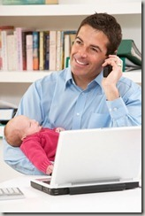 Working Dad Talking On Phone Holding An Infant