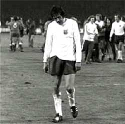 Norman Hunter leaves the pitch dejected as the Polish celebrate behind him.