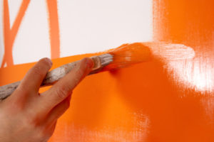 Interior Painting Contractor using brush and orange paint