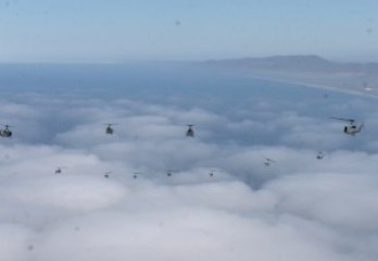 Huey and SuperCobra helicopters fly over coastal clouds during May 4 formation flight./Photo by Cpl. Christopher O'Quin