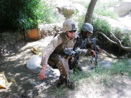 Cpl. Rob Reese, left, a civil affairs Marine with 3rd Battalion, 6th Marines, climbs out of a creek in Marjah, Afghanistan, last week after disposing of ammonium nitrate that Marines found while searching a farm compound. The chemical can be used for fertilizer, but was banned by the Afghan government because insurgents use it to make improvised explosive devices.  Dan Lamothe//Staff
