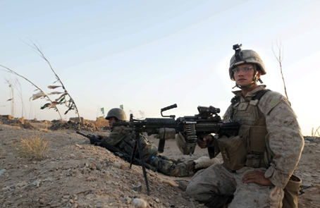 Lance Cpl. Jedadiah Davis, right, and an Afghan soldier sit in a Taliban fighting position just west of Marjah in May. Davis' squad found the positions dug in a ridge at the edge of the Sistani Desert, just west of Marjah.