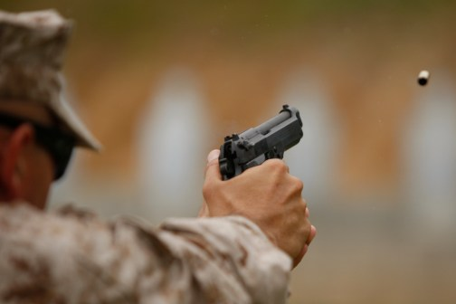A Marine fires an M9 service pistol during training for marksmanship trainers aboard Marine Corps Base Quantico, Va. Some Marines have expressed interest in replacing the M9 with a .45-caliber pistol, and Gen. James Amos told members of Congress he'd like to do the same. (Mike Morones/Staff)