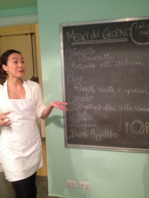 Interpreter standing by chalkboard with the menu written on it