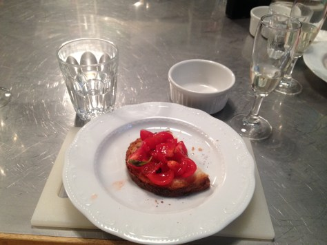 photo of brushetta on white plate with Prosecco glass and water glass