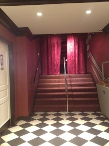 Stairs leading to opening blocked off by red velvet curtains