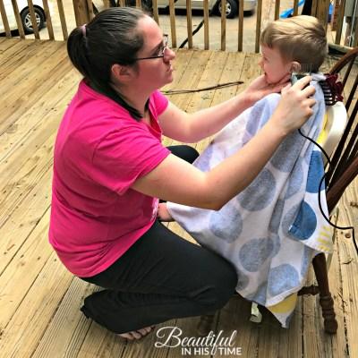 mom giving toddler a haircut