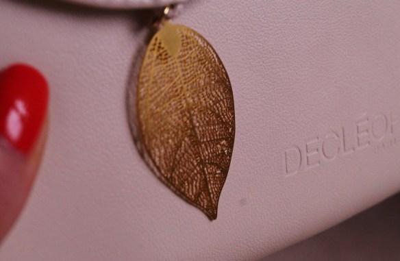 Det tunna vackra guldlövet som sitter vid magnetlåset på Decléors clutch.
