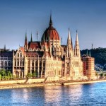 I took many shots of the Hungarian parliament while walking on the opposite shore of the Danube. It was a nice lazy sunny summer afternoon. Processed the shot to enhance the lazy afternoon mood.  The Shot: - ISO 100, 56mm, f5.0, 1/400  Processing: - Photomatix tonemaping on single HDR. - Imagenomics noise reduction. - Unsharp 140 to enhance contrast. - Nik Color Efex Contrast Color Range. - Nik Color Efex Tonal Contrast. - Nik Color Efex Graduated Filter. - Smart sharpen.