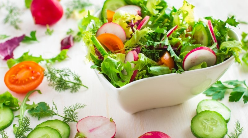 Healthy salad with fresh vegetables and ingredients on white background