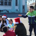 A preschooler plays duck, duck, goose with a group of students from Beverly and Albion Street Elementary.