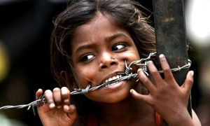 A child bites a barbed wire after a slum fire gutted dozens of huts on Sunday night in an illegal settlement in Chanakyapuri, New Delhi, May 7, 2007. Three people died and four others were injured in the blaze, fire officials said. REUTERS/Desmond Boylan (INDIA)