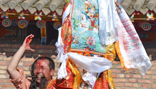 Tibetan Lha-ba, Mountain God Amyes-magpa, who is temporarily manifested in a human medium, holding his hair and a knife with his teeth after cut his forehead.