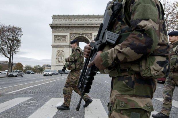 Francuscy żołnierze z bronią przechodzą po pasach przez aleję Champs Elysees w Paryżu.