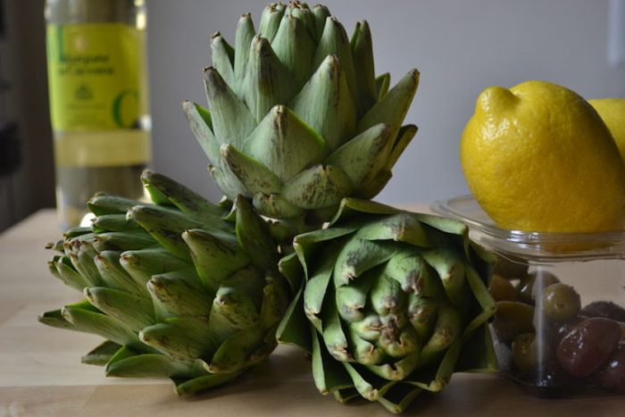 Break down artichokes and braise the hearts with wine and olives. Full recipe on BigTasteTinySpace.com