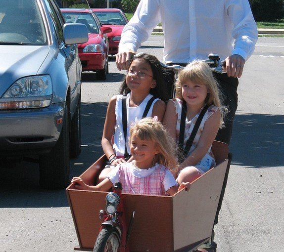 Three children in a bakfiets cargo bike