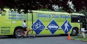 A Spokane Transit bus and a woman on a bike next to it.