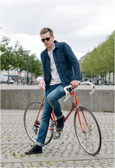Cool young guy wearing jeans, sunglasses, denim jacket on a bicycle.