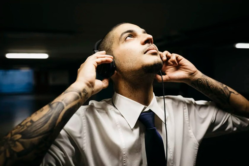 Young businessman with tattoo on his forearms with headphones in a gloomy car park