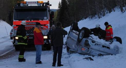 Bil på taket i snöigt dike med bärgare på vägen