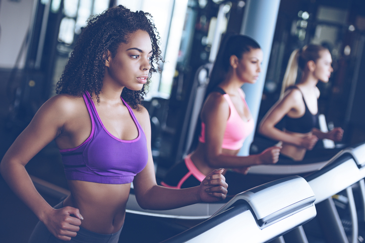 Side view close up of young beautiful women looking away while running on treadmill at gym