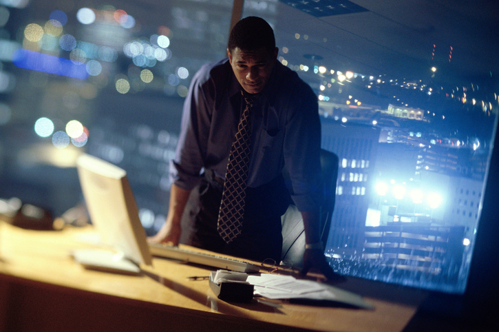 African American businessman standing at desk late night