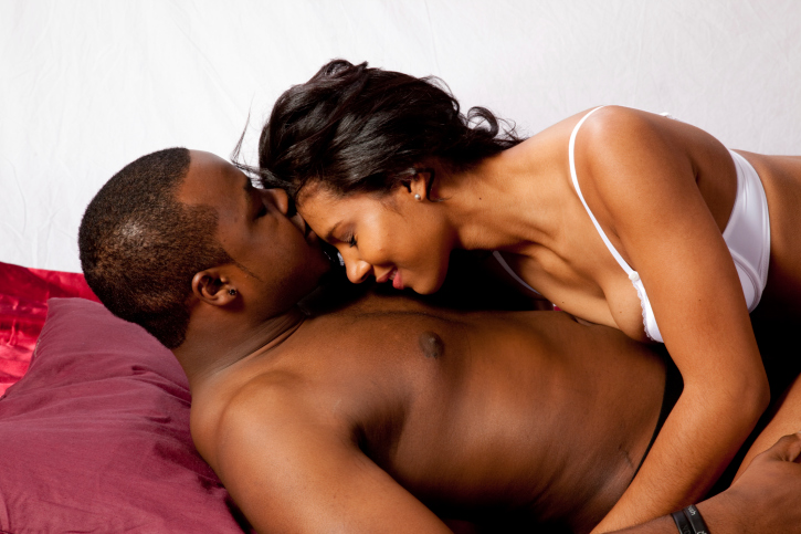 romantic black couple reclining and kissing
