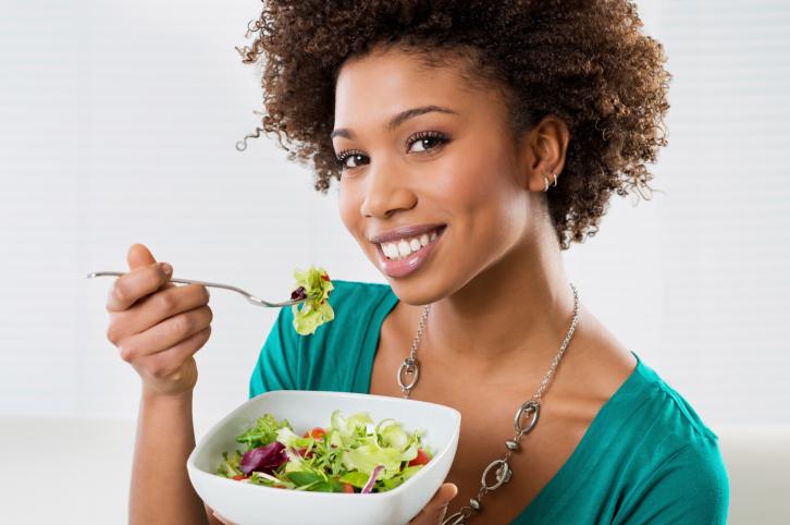 woman eating salad smiling