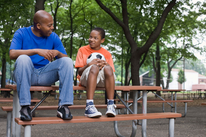 African American man and boy sitting outside on picnic table