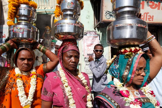 Sidi women carry sacred water on their heads through the town during their communities annual Urs celebration. Happening only once a year and lasting several days they give offerings to their Saint Bava Gor. Jamnagar, Gujarat, India
