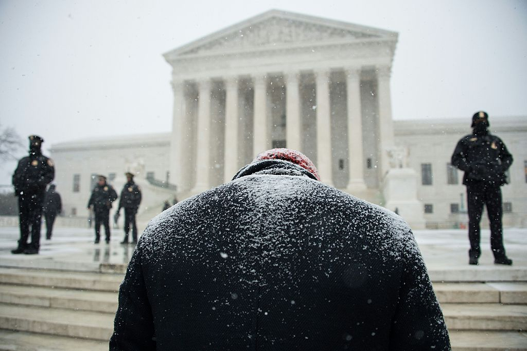 An anti-abortion activist prays during a rally in front of the US Supreme Court in Washington, DC, 0n January 22, 2016 as the country marks the 43rd anniversary of the Roe v Wade Supreme Court decision which legalized abortion. / AFP / Nicholas Kamm