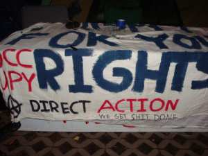 This freshly-painted banner, shown here the night before the arrests, was carried by one of the protestors. (Blast Staff photo/John Stephen Dwyer)