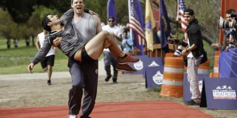 Morgan (Ike Barinholtz) carries Danny (Chris Messina) across the finish line of the titular triathlon.