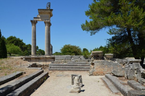 The Hellenistic Bouleteurion with the partially reconstructed temple in the background, Glanum © Carole Raddato
