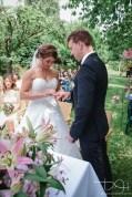 Das Brautpaar steckt sich die Ringe an. Der Hochzeits Fotograf haelt alles auf Bildern fest.
