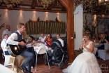 Braeutigam singt ein Staendchen fuer seine Braut. Der Hochzeitsfotograf macht die Fotos.