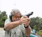 Man shooting a Ruger SR1911 pistol with two spent cartridges in the air