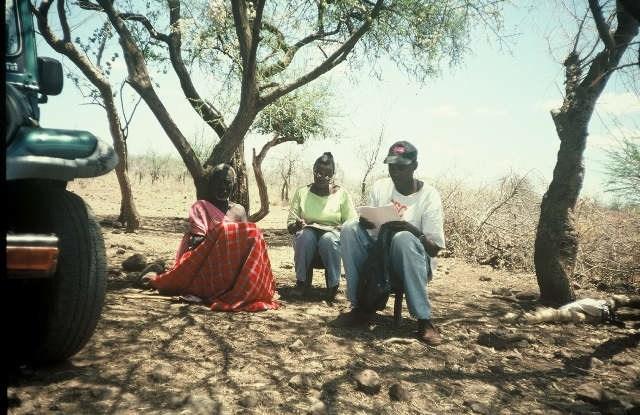 Esther Mwangi (derecha) entrevista a un anciano Maasai en 2001, como parte de su tesis de doctorado sobre el efecto del cambio de los derechos de propiedad de las comunidades hacia los individuos entre las comunidades de pastoreo de Kenia. (Foto: Archivo personal de Esther Mwangi).