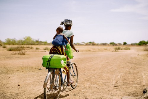 Barry Aliman, 24 years old, rides her bicycle with her baby to collect water for her family, Sorobouly village near Boromo, Burkina Faso.   Photo by Ollivier Girard for Center for International Forestry Research (CIFOR).