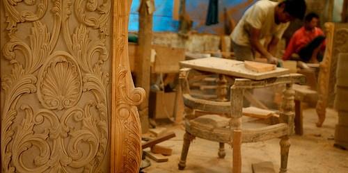 Seorang pengrajin menyelesaikan ukiran di Jepara, Jawa Tengah – pusat produksi furnitur dan kerajinan kayu.
