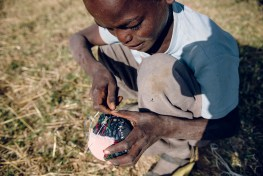A boy makes a small football from cloth and yarn in Koka village, Ethiopia.