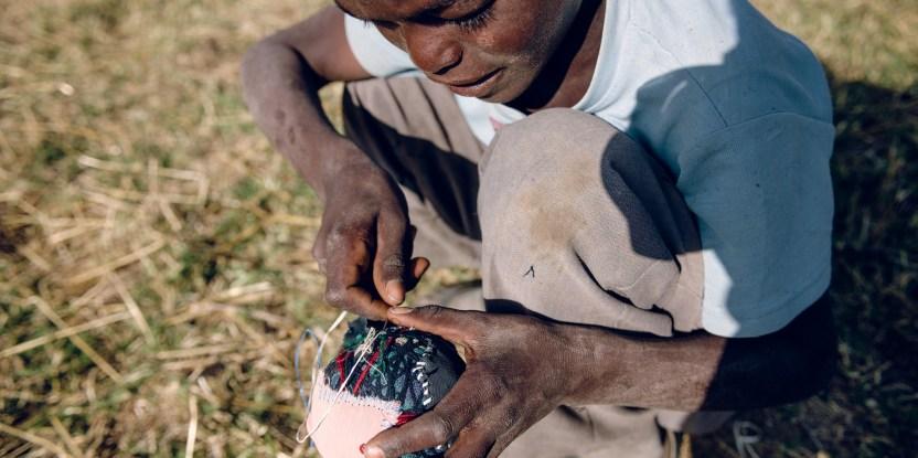 A boy makes a small football from cloth and yarn in Koka village, Ethiopia.