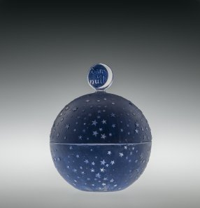Worth Perfume Bottle with Stopper and Box, Worth - 1, Dans la nuit (In the night) Combs-la-Ville or Wingen-sur-Moder, designed 1924 Mold-blown glass bottle and mold-pressed glass stopper, acid-etched, applied patina; original hinged box Bottle: H. 7.6 cm, Diam. 5.1 cm Box: H. 6.3 cm, W. 10.6 cm, D. 7.5 cm 2011.3.290, gift of Elaine and Stanford Steppa
