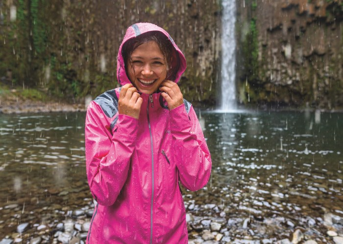 girl wearing pink outdry extreme jacket near a waterfall