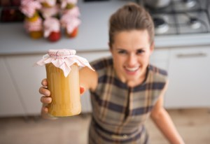 Closeup on happy young housewife showing jar with homemade apple jam