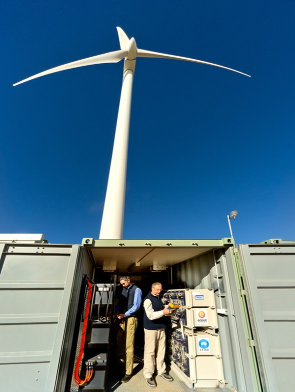 Two researchers in a battery bank underneath a wind turbine.
