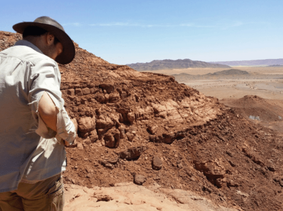 """Ibrahim in the border region between Morocco and Algeria, where he does his fieldwork. """"Getting up here sometimes involves dangerous climbing, including jumps from one rocky ledge to another,"""" says Ibrahim. """"My shirt is showing the first signs of desert climbing wear and tear."""" Photo: Zac Kinney"""